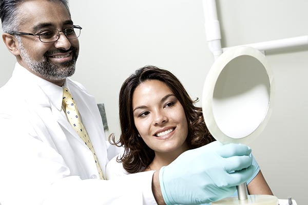 A dentist holding up a mirror for a female patient to see the results of her teeth whitening in Durham, NC