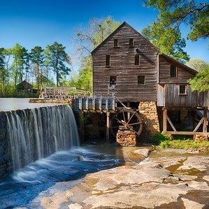 Mill and water wheel being turned by running river.