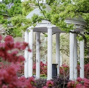 Tress and blossoms frame view of columned summer house in Raleigh, North Carolina.