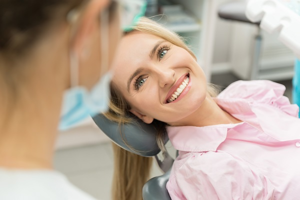 Horizontal color close-up headshot of beautiful woman having dental examination and sincerely smiling at dentist.