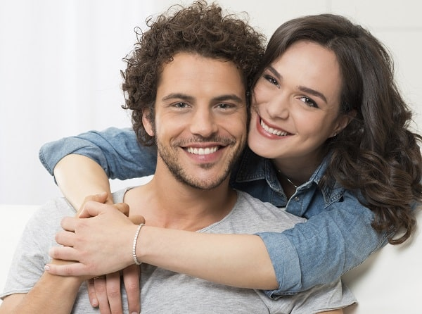Close-up of young couple looking into camera with beautiful smiles due to porcelain veneers