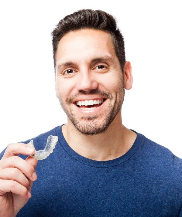 patient holding clear aligners like Invisalign®