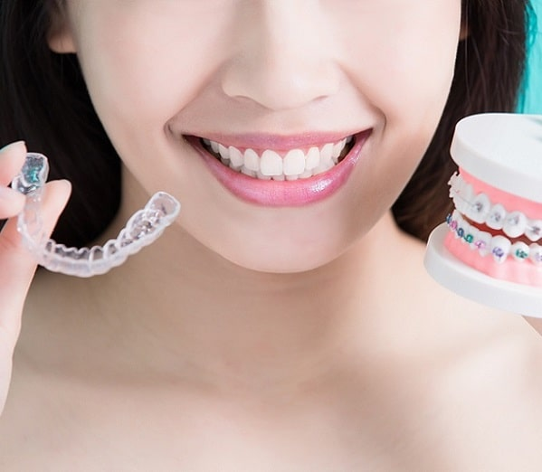 patient holding clear aligners like Invisalign® in Durham, NC
