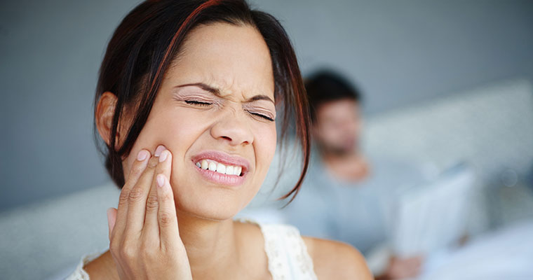 Woman holding her jaw while dealing with dental emergencies.