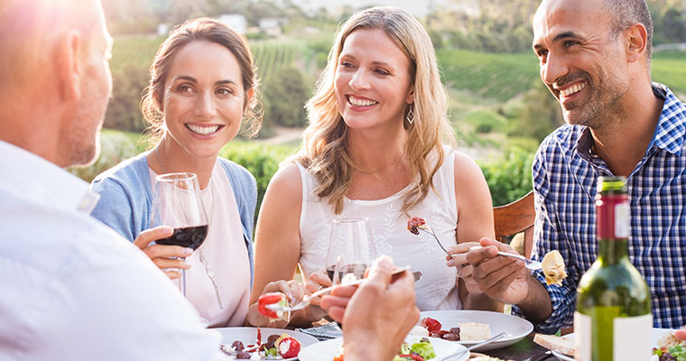Group of two women and two men drinking red wine and enjoying a meal together outside.