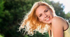 A blonde woman smiling after getting porcelain veneers at Croasdaile Dental Arts
