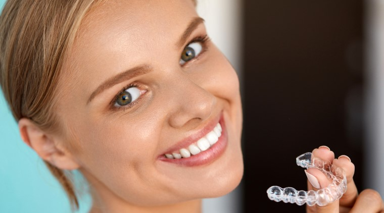 Woman smiling while holding an Invisalign clear aligner